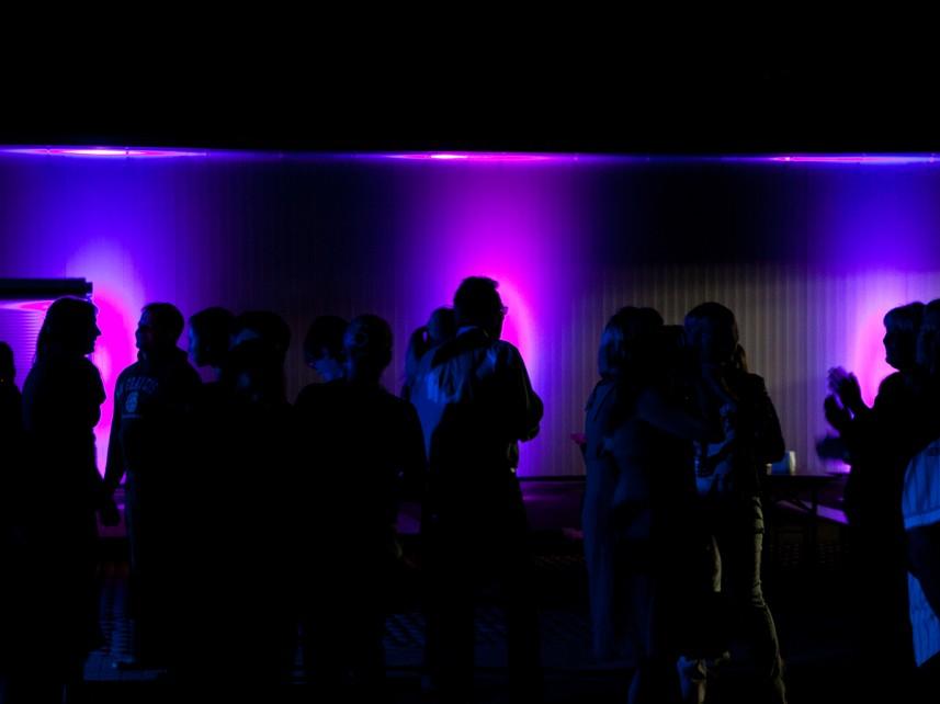Silhouetten vor illuminierter Industriefassade